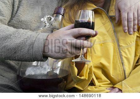 Man and woman sitting together and drinking, outdoor cropped front shot, concept of bad habits and addiction