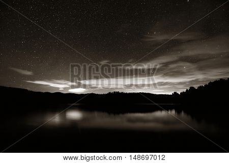 Night with stars in park over lake in Stowe, VT.