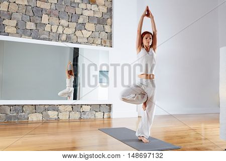Yoga one leg balance Tree pose on wooden floor gym and mirror indoor