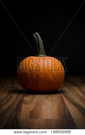 Image of a pumpkin on wood with a black background