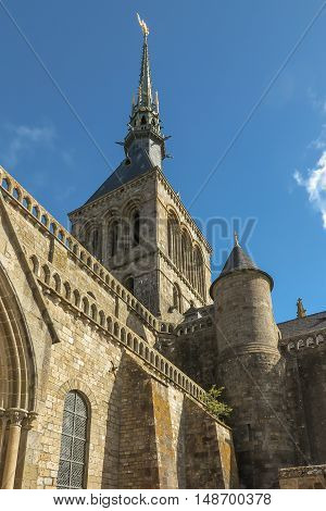 View of famous Le Mont Saint-Michel tidal island on a sunny day with blue sky and clouds Normandy northern France. Old concrete cross.