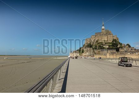 Panoramic view of famous Le Mont Saint-Michel tidal island on a sunny day with blue sky and clouds Normandy northern France