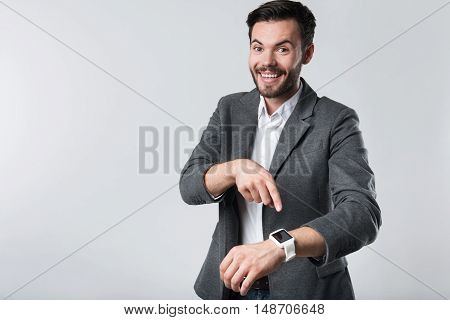 Unbeliveable present. Young good looking bearded man smiling and pointing on his smartwatch, while standing against white background.