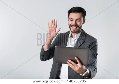 Hallo my friend. Young handsome man smiling and having conversation on his tablet while standing against white background.