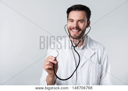 Happy doctor. Young handsome overjoyed man smiling and holding stethoscope while standing against white background.