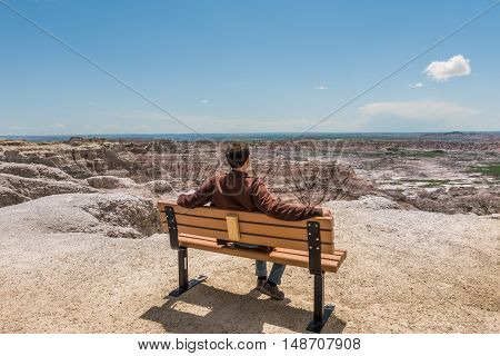 Man sitting on bench looking at view of eroded Badlands canyons in national park
