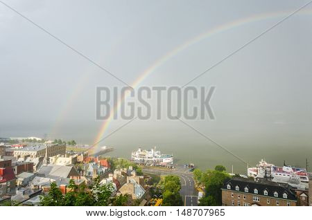 Quebec City, Canada - July 27, 2014: Double rainbow in downtown with view of Saint Lawrence river and boats