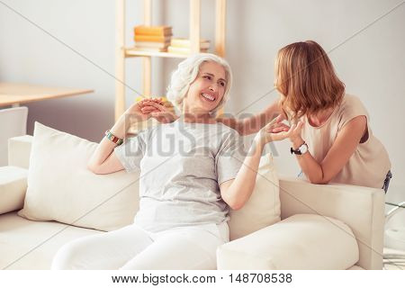 Happy to spend time together. Cheerful delighted aged woman sitting on the settee and having fun with her beautiful daughter