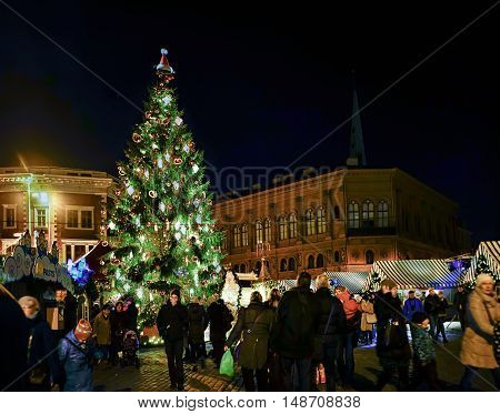 People And Christmas Tree At Market Of Riga Dome Square
