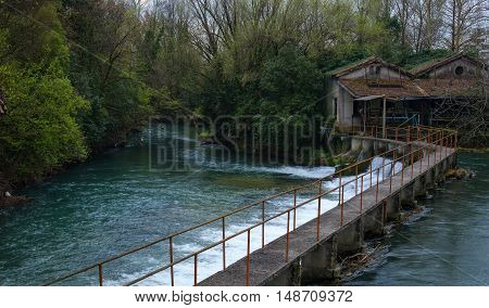 Dam on a small forest river. As laid dam bridge. Bridge comes in two rural homes.