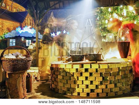 Riga Latvia - December 26 2015: People enjoy a hot traditional meal near the huge pot at Christmas market in Riga Latvia. It is the oldest market in Latvia. Motion blur. Selective focus.