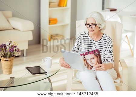 In pace with fashion. Pleasant delighted senior woman sitting in the chair and resting while reading magazine