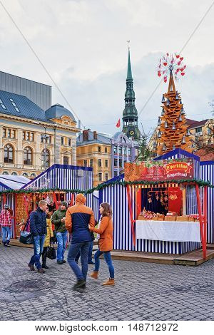 People Walking Near Christmas Market At Livu Square In Riga