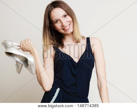 Elegant outfit. Young stylish woman fashionable girl holding silver glitter high-heeled spiked shoes on gray. Fashion and female beauty. Studio shot.