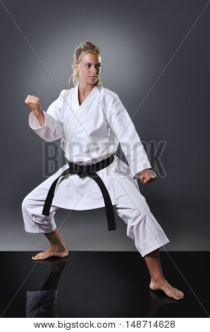 Beautiful young black belt female karate doing kata on the gray background