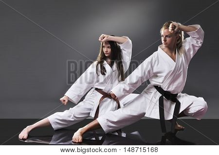 Two beautiful young female karate doing kata on the gray background
