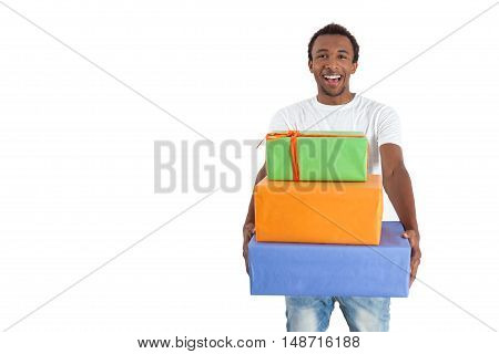 Front view of cheerful African American man holding a stack of packed gifts. Concept of bithday party. Mock up