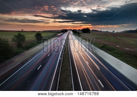 Cars in Motion on Busy Motorway with Colorful Twilight Sky