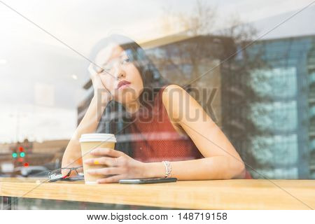 Sad Chinese Woman In A Cafe