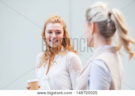 Two Women Walking In The City And Talking