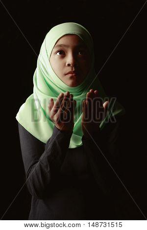 Closeup young muslim girl praying in mosque