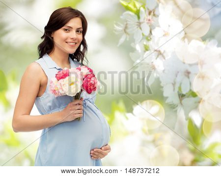 pregnancy, motherhood, holidays, people and expectation concept - happy pregnant woman with flowers touching her big belly over natural spring cherry blossom background