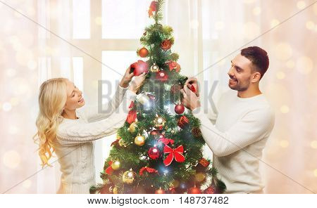 family, x-mas, winter holidays and people concept - happy couple decorating christmas tree at home over lights