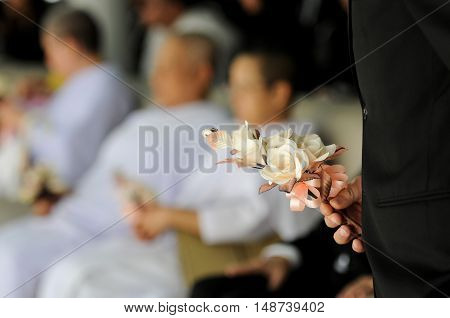 hand hold wood cremation flower, for funeral, background are Guests attending funeral
