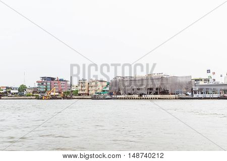 Bangkok Thailand - June 5 2016: Right hand side of Chao Phraya River on cloudy day with construction site. It is at the same side of Siriraj Hospital part of Mahidol university.