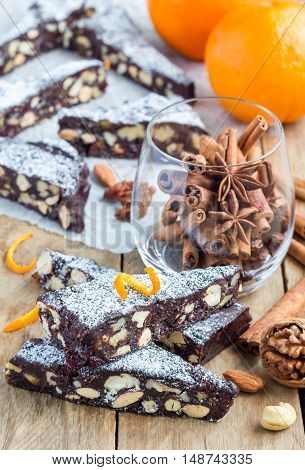 Panforte traditional italian christmas dessert with nuts and candied fruits on parchment vertical