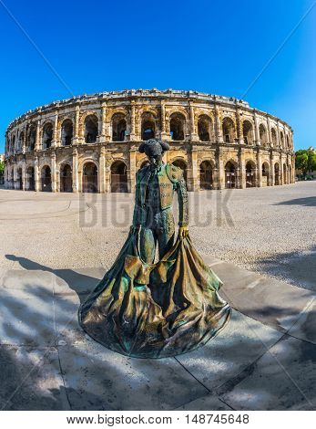 The monument to toreador is placed into square. The Roman amphitheater in Nymes, Provence. The picture is made a lens  Fisheye