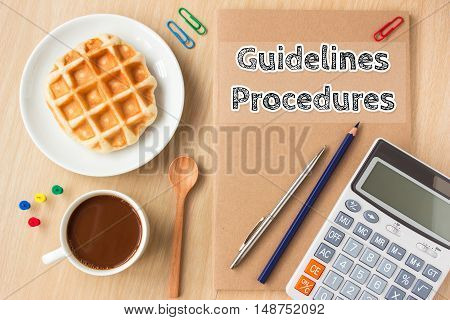 guidelines, procedures text message on paper book and office supplies, pen, coffee on wood desk , copy space / business concept / view from above, top view