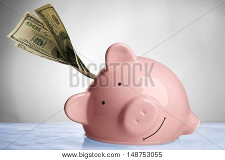 Pink piggy bank with banknote in water on light background. Saving water concept