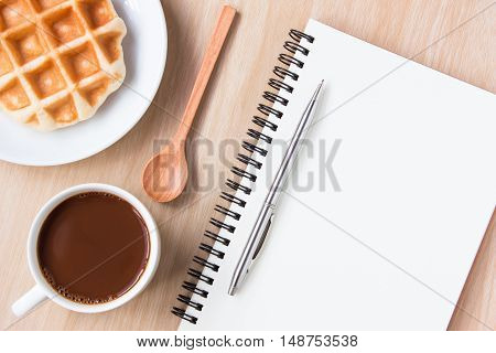 Blank paper and , coffee on wood table background / Open blank white paper notebook with copyspace and a pen lying on a white desk / can be used for your text or artwork / top view