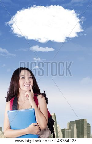Portrait of a beautiful high school student dreaming something while looking at cloud speech