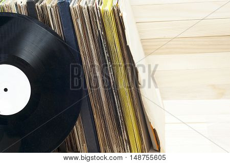 Retro styled image of a collection of old vinyl record lp's with sleeves on a wooden background. Browsing through vinyl records collection. Music background. Copy space. poster