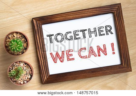 together we can, text message on wood frame board on wood table / business concept / Top view