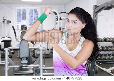 Indian young woman pointing at her bicep in the fitness center while wearing sportswear