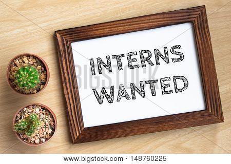 interns wanted, text message on wood frame board on wood table / business concept / Top view