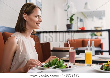 How was your day. Young woman eating salad at restaurant and looking at her interlocutor, smiling
