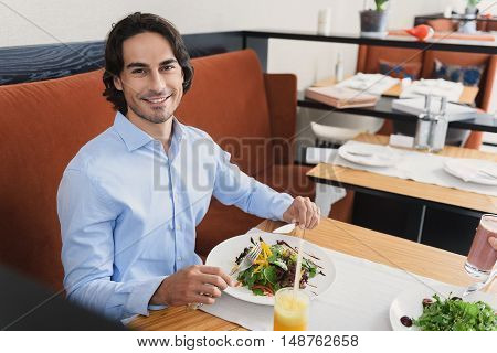 Healthy eating. Handsome smiling man enjoying healthy lunch in cafe while eating salad and looking at camera