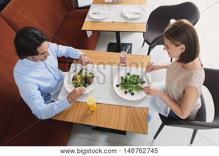 Sharing healthy lifestyle. Top view of happy smiling couple having lunch together at restuarant while eating salad