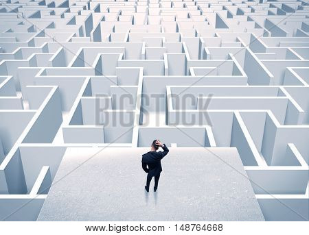 An elegant businessman standing on a square platform looking over infinite labyrinth concept