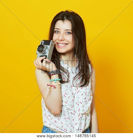 Happy hipster girl with retro camera in studio against yellow background
