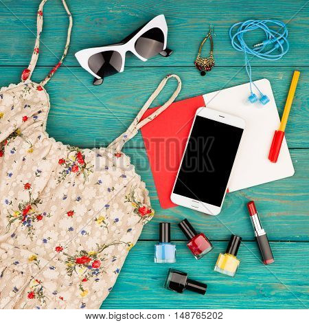 Set Of Woman Stuff With Dress, Smart Phone, Notepad, Accessory And Nail Polishes On Blue Wooden Desk