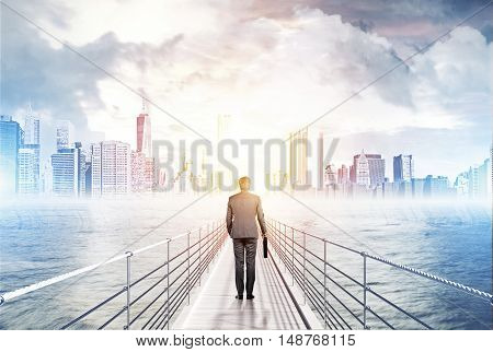 Rear view of businessman with briefcase standing on bridge in ocean and looking at large city panorama. Concept of future prospects in business. Toned image