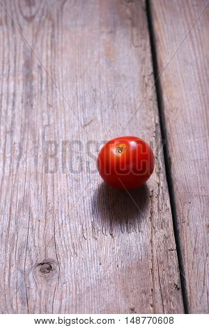 Single red tomato on a wooden background.