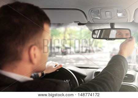 Businessman driving a car and looking into rear view mirror