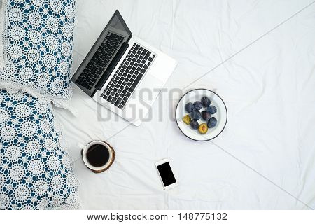 Working In Bed , Laptop And Cup Of Coffee On White Bed