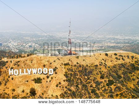 LOS ANGELES, USA - MAY 27, 2015: Aerial view of the Hollywood Sign on Mount Lee on top of the mountain several antennas in the back Warner Bros. Studios and Forest Lawn Hollywood Hills cemetery.